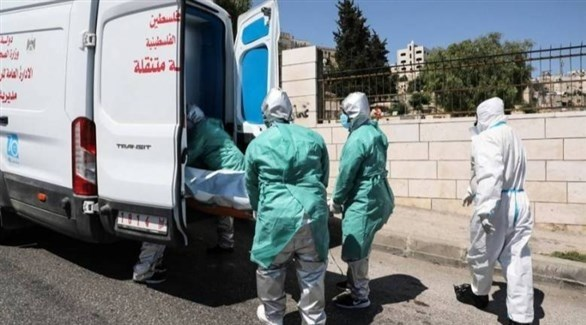 عاملون في قطاع الصحة الفلسطيني ينقلون جثمان أحد ضحايا كورونا (أرشيف)