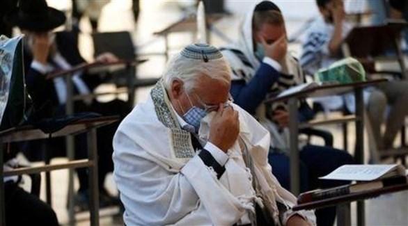 السفير الأمريكي ديفيد فريدمان يضع كمامة على وجهه بينما يصلى عند حائط المبكى (رويترز)