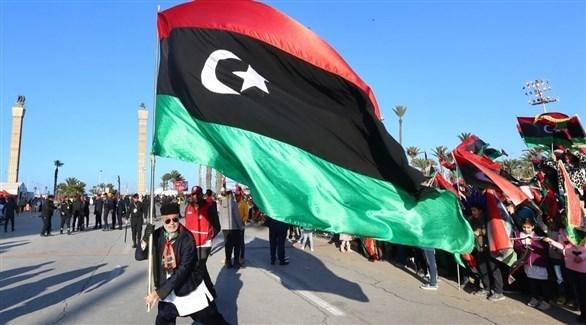 شخص يرفع العلم الليبي خلال أحد التجمعات (أرشيف)