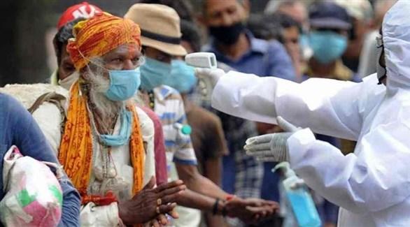 عامل في القطاع الصحي يقيس حرارة مُسن هندي (أرشيف)