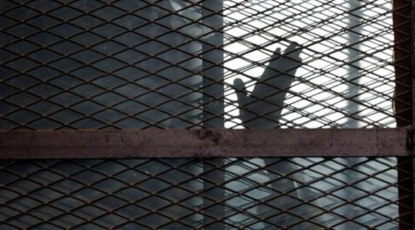 مسجون يرفع يده خلف الشباك الفاصل (أرشيف / أ ب)