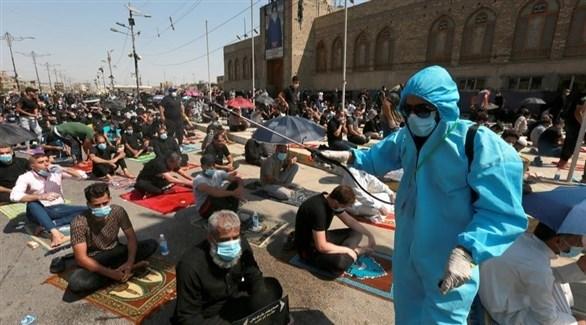 عامل يرش مصلي الجمعة في مدينة الصدر بمعقم (إ ب أ)