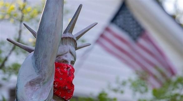 كمامة ملفوفة على وجه نسخة من تمثال الحرية (إ ب أ)