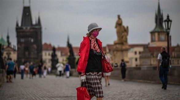 سيدة إسبانية ترتدي الكمامة للوقاية من كورونا خلال جولة خارج منزلها (إ ب أ)