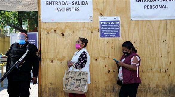 شرطي مكسيكي مع سيدتين أمام مركز صحي لكشف كورونا (أرشيف)