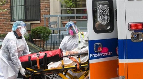 مسعفان أمريكيان ينقلان مصاباً بكورونا إلى سيارة إسعاف (أرشيف)