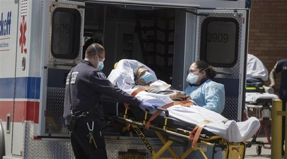 عاملان في القطاع الصحي الأمريكي ينقلان مصاباً بكورونا إلى سيارة إسعاف (أرشيف)