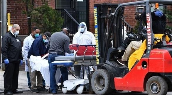 مسعفون أمريكيون يضعون جثة متوفى بكورونا على رافعة شوكية (أرشيف)