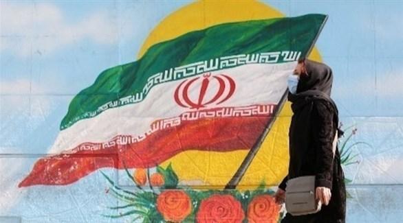'إيرانية تسير بجانب جدارية لعلم بلادها (أرشيف)