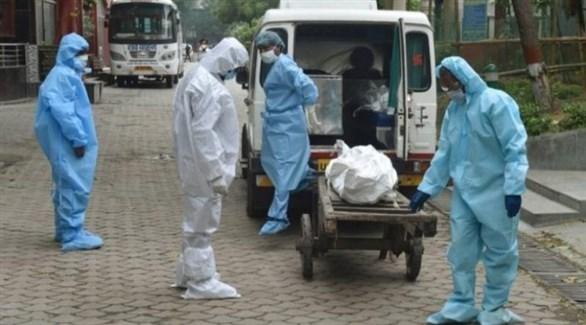 أطباء هنود يضعون جثة متوفى بكورونا داخل سيارة إسعاف (أرشيف)