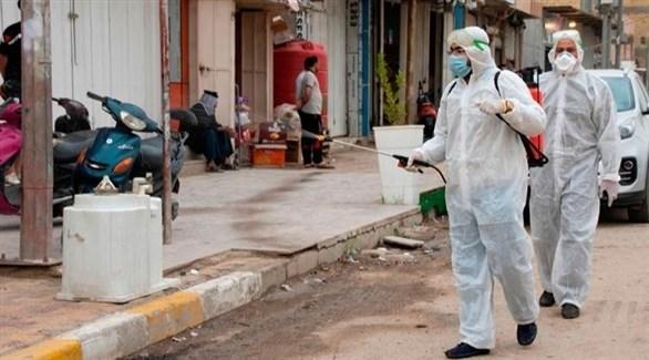 عمال يعقمون شارعاً بالعراق (أرشيف)