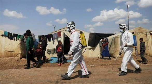 عاملون بقطاع الصحة يعقمون خياماً للاجئين سوريين في شمال البلاد (أرشيف)