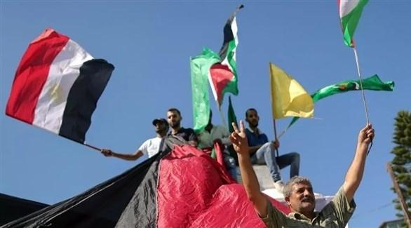 فلسطينيون يرفعون أعلام مصر وفلسطين  وفتح وحماس (أرشيف / أ ف ب)