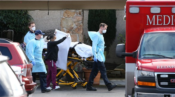 عاملون في القطاع الصحي الأمريكي ينقلون جثة أحد ضحايا كورونا إلى سيارة إسعاف (أرشيف)