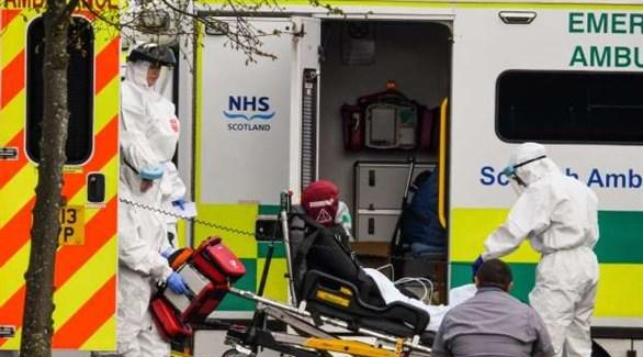 مسعفون في اسكتلندا ينقلون مصاباً بكورونا إلى سيارة إسعاف (أرشيف)