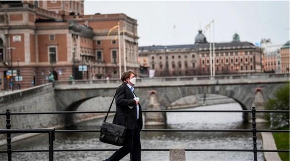 رجل يرتدي كمامة أثناء مروره وسط ستوكهولم (أرشيف)
