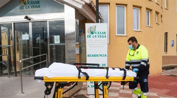 عامل في دار رعاية مسنين إسبانية ينقل جثة أحد ضحايا كورونا (أرشيف)