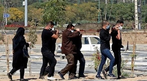 إيرانيون يحملون جثمان متوفى بكورونا استعداداً لدفنه (أرشيف)
