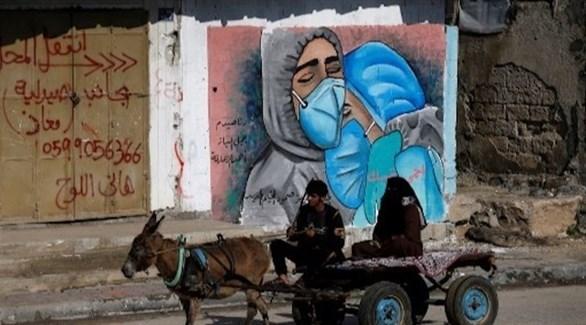 حمار يجر عربة يركبها فلسطينيان يمر بجانب جدارية لدعم الكوادر الطبية بغزة (أرشيف)