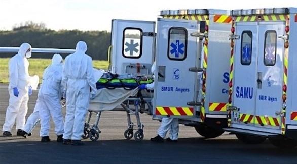 مسعفون فرنسيون ينقلون مصاباً بكورونا لإحدى المستشفيات (أ ف ب)