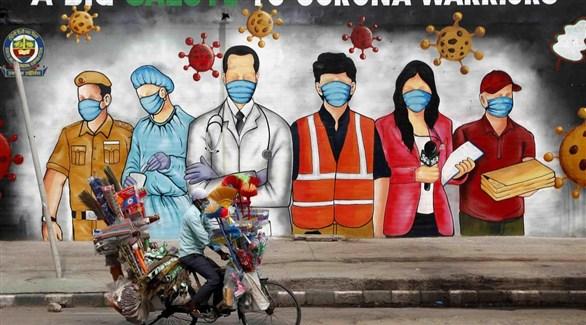 هندي على دراجة أمام جدارية لشكر فرق مكافحة كورونا (أرشيف)