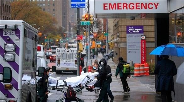 مسعفون أمريكيون ينقلون مصاباً بكورونا أمام طوارئ مستشفى (أرشيف)