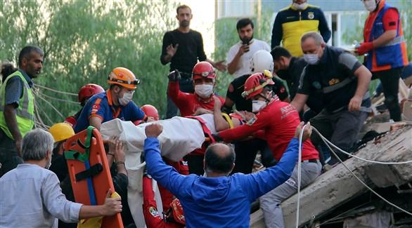 مسعفون ومنقذون يستخرجون ناجياً من تحت أنقاض مبنى في إزمير (أ ب)