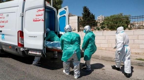 فلسطينيون ينقلون جثة أحد كورونا إلى سيارة نقل الموتى (أرشيف)