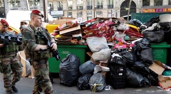 جنديان يمران بجانب كومة من النفايات في فرنسا (أرشيف)