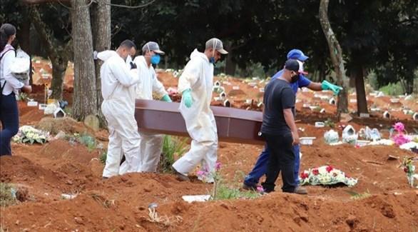 عمال في مقبرة برازيلية ينقلون تابوت أحد ضحايا كورونا (أرشيف)