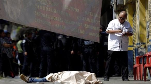طبيب شرعي قرب جُثة أحد ضحايا العنف في المكسيك (رويترز)