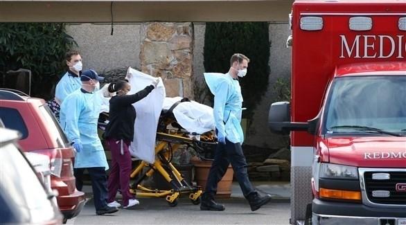 عاملون صحيون ينقلون أحد ضحايا كورونا في أمريكا إلى سيارة إسعاف (أرشيف)