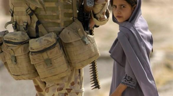 طفلة تقف إلى جانب جندي (أرشيف)