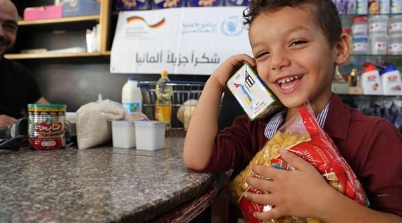 طفل فلسطيني محملاً بمساعدات غذائية ألمانية (أرشيف)