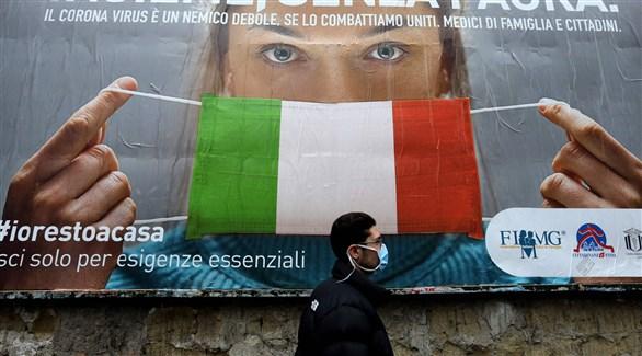 إيطالي أمام جدارية للتوعية بخطورة الوباء في ميلانو (أرشيف)