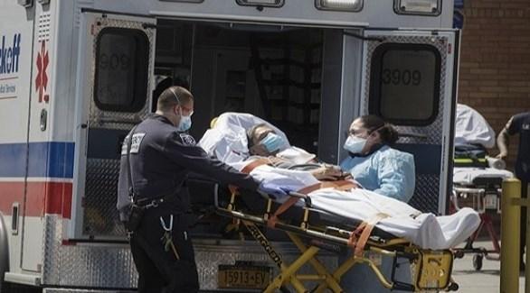 مسعفان في نيويورك ينزلان مصاباً بكورونا من سيارة إسعاف (أرشيف)