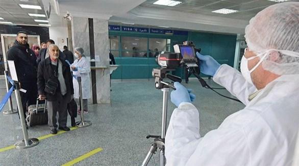 عامل صحي يفحص حرارة مسافرين في مطار تونس قرطاج (أرشيف)