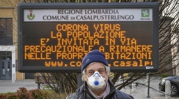 إيطالي في لومبارديا أمام لوحة تدعو إلى البقاء في المنازل لتفادي كورونا (أرشيف)