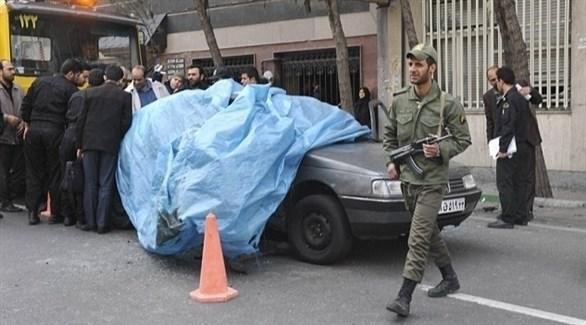 أمنيون وعسكريون حول سيارة العالم النووي الإيراني مصطفى أحمد روشن بعد اغتياله (أرشيف)