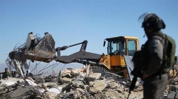 جندي يقف قبالة جرافة إسرائيلية (أرشيف)