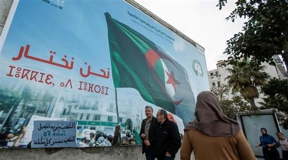 جزائريون أمام جدارية تدعو للمشاركة في الاستفتاء (أرشيف)