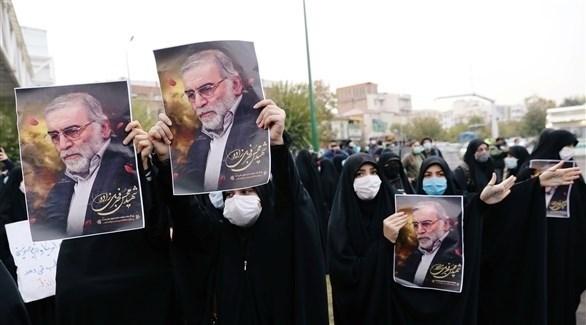 نساء يرفعن صور العالم الإيراني خلال مراسم التشييع (أرشيف)