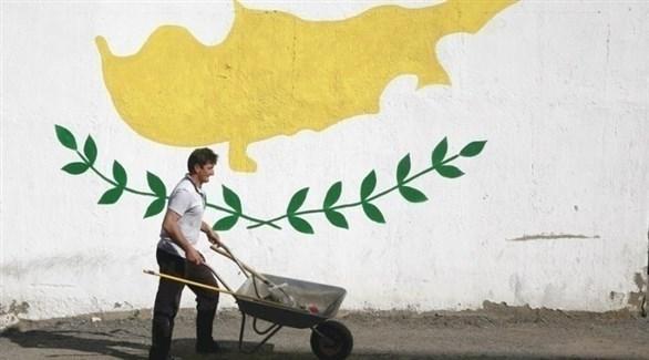 رجل يمر بجانب رسم مضخم للعلم القبرصي (أرشيف)