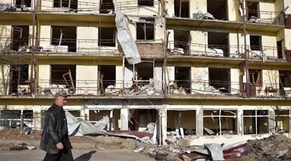 رجل يمر بمحاذاة مبنى مدمر جراء القتال في ناغورنو قرة باغ (أرشيف)