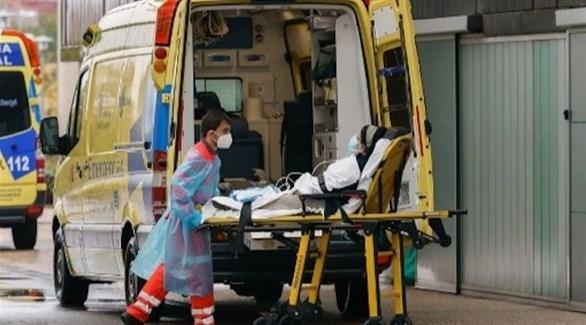 مسعف إسباني ينقل مصابة بكورونا للمستشفى (أرشيف)