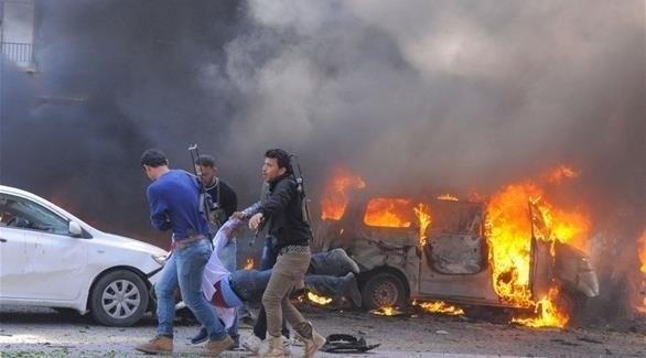 سوريون حول سيارة مشتعلة بعد تفجير سابق (أرشيف)