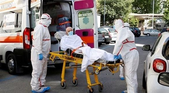 مسعفان ينقلان مصابا بكورونا إلى سيارة إسعاف (أرشيف)