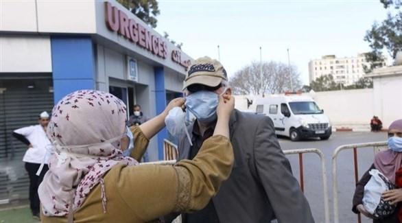سيدة تساعد رجلاً على ضبط كمامته أمام مستشفى في الجزائر (أرشيف)