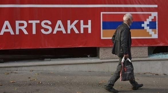 أرمني يسير بمحاذاة جدارية مكتوب عليها آرتساخ أو قرة باغ (أ ف ب)