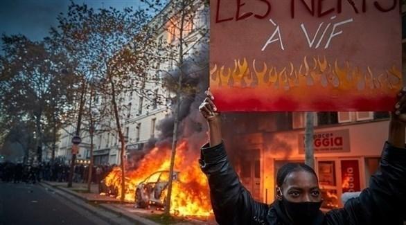 متظاهرة أمام سيارات مشتعلة في فرنسا (أرشيف)